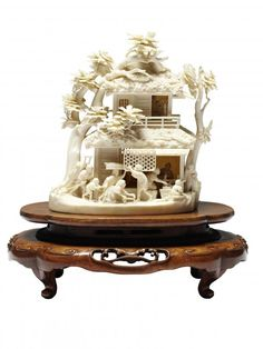 Japanese ivory okimono Depicts figures at various pursuits around a building. c1900  Signed