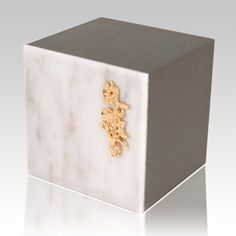 The Expressionism White Danby Marble Cremation Urn with the sides in brushed light bronze it is assembled from real natural quarried stone. This wonderful natural stone urn will create a dignified resting place for eternity to come.
