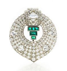Art Deco Diamond and Emerald Clip, Cartier   Platinum, white gold, the modified bombe circular mount topped by a stepped panel centering one emerald-cut diamond approximately .95 ct., flanked by 2 shield-cut diamonds approximately 1.00 ct., supporting 5 square and rectangular-cut emeralds, highlighted by 4 round diamonds approximately 2.15 cts., set throughout with 173 old European and single-cut diamonds approximately 7.00 cts., signed Cartier, # 3615674, circa 1935