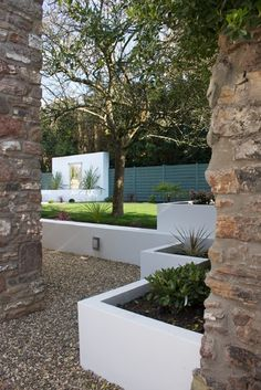 Low smooth coat planter walls, gravel and drought tolerant plants