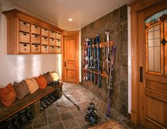 8 Ideas for High-Functioning Mudrooms ||  Seasonal storage. Mudrooms can be the perfect place in which to store outdoor sports gear for all four seasons, with the right organizational techniques. This ski-loving family came up with a great solution to keep their winter gear under control: Cubbies for gloves and hats up top, spots for boots below the bench and custom ski racks keep everything neat and tidy.
