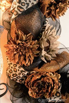 This elegant autumnal look features black and gold deco mesh, printed burlap ribbon—and a surprise appearance by a sassy, black feather boa.