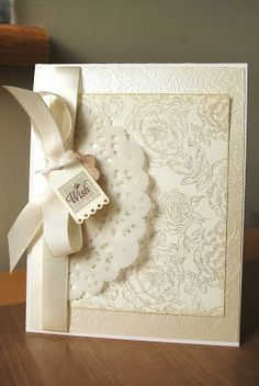 Supplies; Stamps; Background roses, Tiny Tags, Paper - vellum(doily), cream, shimmer, Other; Parisian doily die, Tiny Tags die, In Bloom impression plate, Antique linen distress ink, cream satin ribbon, 1/8'' silk ribbon.