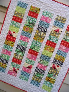"Fast and easy baby quilt.  This quilt was made without a pattern. The ""coins"" were cut 2.5"" x 4.5"" and they are stacked 15 high. There are 5 stacks of 15 coins.  The sashing in between coin stacks were cut as a 1.75"" strip.  The left and right hand side borders were cut as a 3.5"" strip, and the top and bottom borders as a 5"" strip."