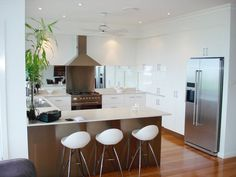 U-shaped with breakfast bar. White gloss cupboards.