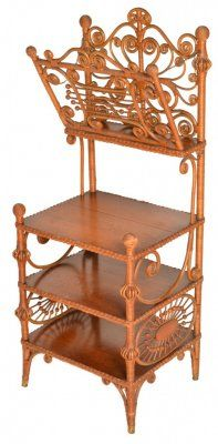 """Victorian wicker music shelf or magazine stand.   Shown on p. 100 of """"Heywood Brothers and Wakefield Company, Classic Wicker Furniture, The Complete 1898-1899 Illustrated Catalog."""" It features a great top with many curlicues, birdcages and stick and ball work. A front piece is hinged and folds out while supported by small chains on both sides. The base has three oak shelves with ornate embellishments. Small fragment of the original red label on the bottom.   Circa: 1890.  49″H x 19″W x 16″D"""