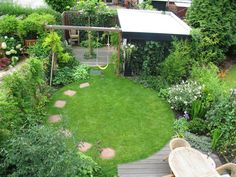 Small garden design integrates a central circular lawn with a curved edge deck, play area, shed and second seating area.