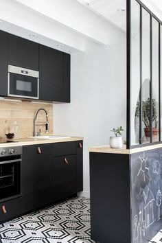 Industrial kitchen with separating canopy. Black furniture and credence in light wood. Tile with geometric patterns Source by kaytleenmeriotte Black Furniture, Kitchen Furniture, Kitchen Dining, Kitchen Decor, Family Kitchen, Kitchen Pictures, Black Kitchens, Küchen Design, Kitchen Remodel