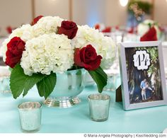 White hydrangea and red rose centerpiece in silver vase. Cute table numbers as well!
