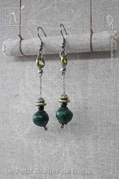 Réalisation [ Fait-Main ] avec du fil aluminium (Ø2mm), une perle en malachite, une perle de rocaille et une  perle tibétaine, ainsi qu'une perle d'acier inox et deux anneau d'aluminium. Les crochets d'oreilles sont en acier inoxydable ainsi que la chaîne. Petites boucles d'oreilles ou boucles d'oreille à assortir avec tenue et maquillage, selon l'envie. Facile à mettre et enlever, la boucle d'oreille est légère et se dandine au gré des mouvements, avec de petits tintements agréables qui...