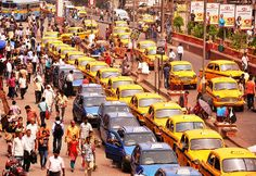In front of Howrah railway station- a busy crowded place in India. Yellow Ambassador Taxi and blue colour cabs are in line in taxi stand to catch the passengers.