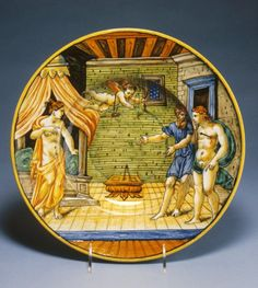 An Italian maiolica dish portraying King Candaules exhibiting his wife, Nyssia, to Gyges; Cupid has wounded Gyges with an arrow, symbolising love at first sight. (Walters Museum)