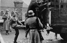A member of the German police kicks a Jew who is climbing onto the back of a truck during a round-up for forced labor. Two other Germans look on with derision.