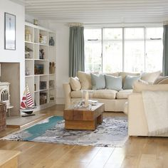 Coastal-style living room ~ Shades of aqua and sand are used in this living room to create a calming seaside scheme. Light cream sofas go well with natural wooden flooring and an earthy coffee table. Built in storage is useful to keep clutter at bay, while a model boat flanks the simple fireplace to continue the theme....