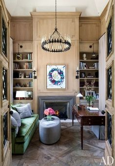 The oak-paneled library in Gisele Bündchen and Tom Brady's home includes a Dessin Fournir chandelier and sconces, the latter flanking a work by Sam Francis above the fireplace; the sofa pillows are made of a Loro Piana fabric | archdigest.com