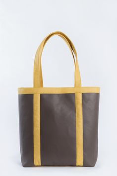 """The shiitake tote features the vegan leather in both the shiitake and  goldenrod colors. The soft durable material makes it the perfect everyday  bag. And the splash of color is perfect for spring and summer wear.  With the two compartments and waterproof recycled nylon, the tote can carry  both your purse and """"activity"""" items."""
