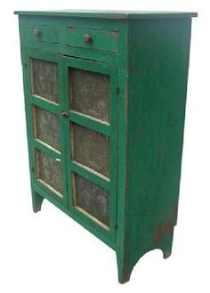 Y204 19th century Floyd County Virginia, Pie Safe,with early imerial green paint over the original red, Two doors that is mortised, with six hand punched tins, the pattern of the tins is a large six peddle flower, inside of a punched boarder. Two dovetailed drawers, one board ends, natural patina on the inside. circa 1840