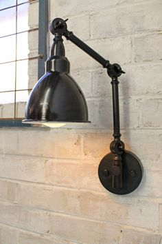 This industrial style two arm swing wall lamp has a huge range of movement and comes with a choice of shade colours