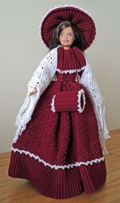 Doll Information: The Christmas Caroler doll is based on a pattern published by Paradise Patterns. She is made primarily with burgundy cotton crochet thread. Her trim is of a white cotton crochet thread. Her shawl is made of white cotton crochet thread. This doll includes: •One doll from the Barbie and Friends Collection •Gown •Bonnet •Shawl •Petticoat •Pantaloons •Muff •Shoes