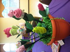 """Baby shower centerpiece/gift... Each """"bloom"""" is made of a baby item (onesie, bib, socks, hat, etc.)... Roll item into a flower and then use floral wire to keep it in its shape; use floral tape to secure to green stick and cut leaf out of green paper. Arrange them into flower pot by putting stick into foam (placed in pot) then add green paper (Easter grass worked great) for grass. We added packs of seeds to bright garden gloves and favors to go along with the garden theme!"""