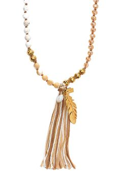 This lengthy luxe necklace includes semiprecious stones, crystal, and golden metalwork, plus the fun element of a soft tassel.