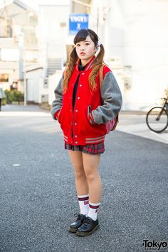 19-year-old Acane on the street in Harajuku with a twin tails hairstyle, a resale stadium jacket, a plaid skirt, and Dr. Martens shoes with striped socks.