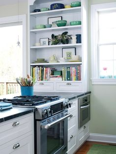 Why not bring a bookcase into the kitchen? Here, a built in storage unit displays colorful cookbooks and serving pieces.
