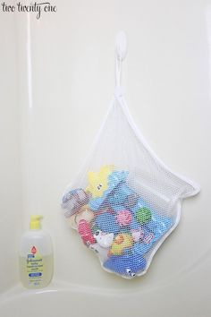 Nursery & Baby Organization Tips - Mesh Laundry Bag + Command Hook (or suction cup hook) = DIY Bath Toy Organizer