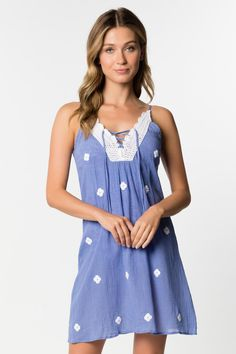 This beautifully made trapeze dress in a soft cotton is perfect for a seaside lunch or a walk into town. A scalloped crochet V front and back with double tassel ties bring a hint of flair to this alluring embroidered piece. -crochet scalloped V neck and back -criss-cross tie tassel ends -white flower embroidered -gold beading -hits mid-thigh