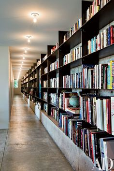 """The entire north wall of the house's lower level is lined with 100 feet of steel shelving that holds the owners' extensive library. """"Tom doesn't hide behind cleverness or decoration in getting it right,"""" observes Schneider."""