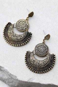 "Take the Live Show Gold Earrings out for a night on the town! These unique antiqued gold earrings have swirling, engraved accents. Earrings measure 2"" long."