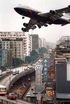 Boeing 747 over HK. It felt like I was flying down a street when landing at Hong Kong; at least it did in a 747 back in 1974. Since the runway extended out into the bay, it looked, at first, like we were going to ditch in the water then the next thing I knew we were flying down a street looking up at laundry hanging out to dry!