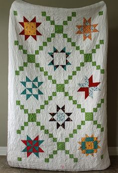 Star sampler quilt-- I love the chain going through this quilt with a star in each section.  I'd prefer one type of star instead of a star sampler, though.-- possible pattern?