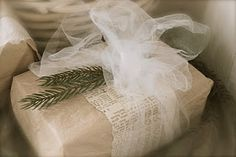 gift wrapping using tulle, book page, and a sprig of something fragrant