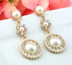 """Bridal Earrings Wedding Earrings Wedding by goddessdesignsgems, $39.00 """"Breathtakingly beautiful"""" these earrings are nothing short of stunning! Showcasing a designer inspired design with an incredibly unique drop style with a white pearled background rimmed with gold accents and clear glistening Austrian crystals interspersed throughout the design."""