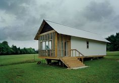 large screened porch shares the home's single metal roof, simple inexpensive structure