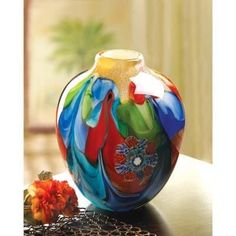 Floral Fantasia Art Glass Vase This individually hand crafted jug-shaped vase is a treasure of glowing color and graceful garden imagery. Actual item may vary in colors from the picture shown here.