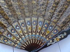 Description: Vintage Abanico Giner Spanish ladys fan. This lovely fan is primarily gold covered in a sheer black lace with a lovely hand painted blue, orange and gold floral motifs at the celluloid base. There is also the same ornate painting on the guardsticks at the sides. This is a medium size Flamenco style fan and would fit perfectly in a larger handbag. There is a black tassel at the end which hangs form a gold tone loop. Measurements: Span is approximately 58 cm or 23 inches…