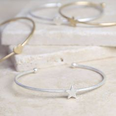 Add an edge to your stack with a delicate heart or star bangle from Lisa Angel Jewellery.<ul> <li>Delicate ladies' matt gold or silver bangle.</li> <li>With a dainty heart or star charm attached to the centre.</li> <li>Open at the back and can bend slightly to fit on the wrist.</li> <li>Gold or silver plated.</li> <li>From the Lisa Angel Jewellery Collection.</li> </ul> Whether it's an elegant touch, a bold statement embellishment or that truly personal gift, we've got it all here at Lisa…