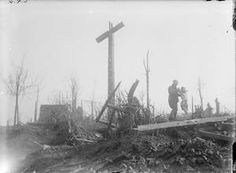 WWI, 21 March 1917; British soldier lifting damaged christ figure from ruined calvary at Le Barque, n-w of the Butte de Warlecourt. ©IWM Q 3874