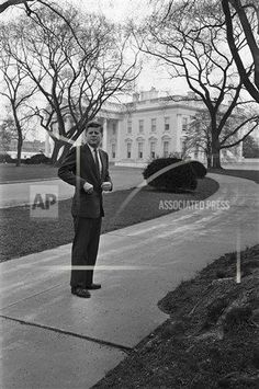 President John Kennedy, standing in a drive before walking back to the White House, Washington on March 5, 1961, watches an automobile bearing departing guests. The President walked to the gate with his guests, followed their departure and then returned to the Mansion. (AP Photo/RHS)