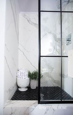 The powder-coated steel on the shower door is repeated on the custom mirror. Black floor tiles from Crossville anchor the sleek oasis. - Photo: Brittany Ambridge / Design: Laura Burleson