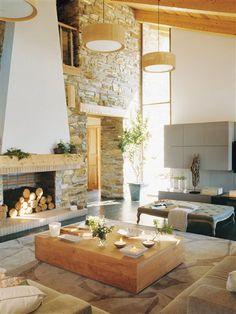 Un salón con chimenea    Mesa de centro de teca natural, de Batavia. Sobre ella, bandeja blanca de la misma firma. La banqueta es de Becara.