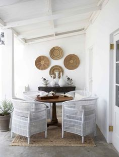 Back stoep with beaded vessels by Serpentine and rug by Gonsenhausers. Malawian chairs painted white. Interiors by Jean-Pierre de la Chaumette.