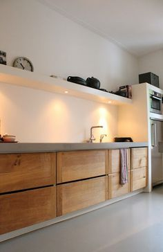 Bespoke cabinets. Big fan of drawers below instead of cupboards. Clean lines good lighting. Concrete tops?? Love.