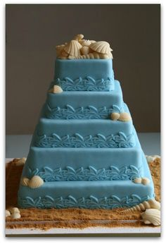 Ditch the traditional white wedding cake in favor of a bright color that is still classy but will show off your personality and color palette beautifully.  Love the faux sand detail too:)