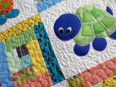 Bright yellow a splash of green and everything in between are colors to describe this non traditional colored baby quilt. Satin stitched appliqued