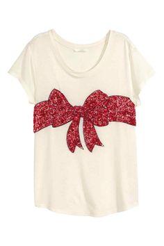 T-shirt con paillettes: T-shirt a maniche corte in morbido jersey. Ricamo con paillettes davanti.