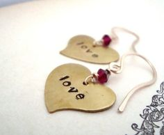 """Hand Stamped Heart Earrings. I made these earrings with those who want to spread the love, or bring it their way! A heart shaped brass hand-stamped medallion horizontally displays the words """"LOVE"""". I"""
