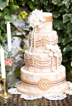 Fondant-covered wedding cake is draped in sugar flowers and pearls. Jennifer Kloss Photography.